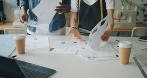 Les gens travaillant de mode concevant le studio tenant des croquis recherchant des idées clips vidéos