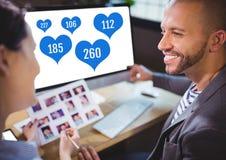 Les gens travaillant sur l'ordinateur dans le bureau avec des goûts dans des icônes de coeur Image stock