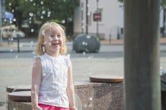 Les gens, une petite fille jouent heureusement à la fontaine pendant la saison chaude d'été Image stock