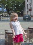Les gens, une petite fille jouent heureusement à la fontaine pendant la saison chaude d'été Image libre de droits