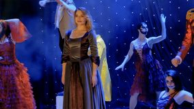 Les gens utilisant les costumes scéniques sont chantants et dansants sur l'étape dans le théâtre banque de vidéos