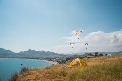 Les gens volant sur des parapentistes en mer Photos stock