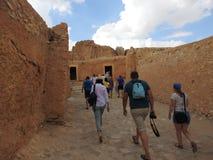 Les gens, vue de dos, vont à l'oasis de montagne de Chebika avec des palmiers dans le désert du Sahara arénacé, ciel bleu bleu, T image libre de droits