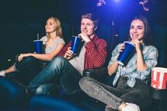 Les gentilles personnes s'asseyent ensemble dans une salle de cinéma Ils boivent le coke et ont l'amusement Tous sourient et Photos stock