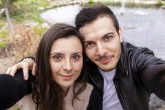 Les gentils amis de couples en parc prend un selfie Photo stock
