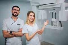 Les gentils dentistes positifs se tiennent dans la chambre de rayon X Homme et pose et sourire de femme Elle se dirigent sur la m image stock