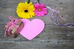 Les Gerberas fleurit avec le boîte-cadeau, le coeur de papier et les bandes colorées sur le bois Photographie stock libre de droits