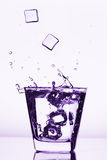 Les glaçons éclaboussant dans le verre, glaçon se sont laissés tomber dans le verre de l'eau Image stock