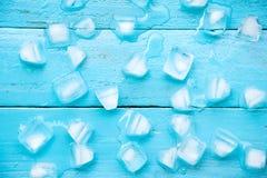 les glaçons froids sont fonte partielle sur le fond en bois bleu Photographie stock