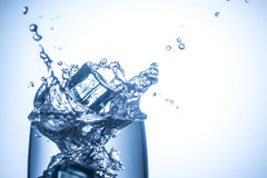 Les glaçons tombant en verre avec de l'eau éclabousse haut étroit Image libre de droits