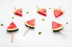 Les glaces à l'eau et le papier de tranche de pastèque monnayent sur le backgr en bois blanc Photos libres de droits