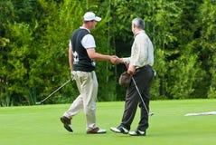 Les golfeurs se serrent la main Photographie stock