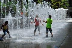Les gosses battent la chaleur - refroidissez dans la fontaine d'eau Images stock