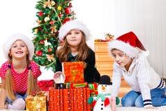 Les gosses s'asseyent près des cadeaux de Noël Images libres de droits