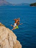 Les gosses sautant dans l'eau Photographie stock libre de droits