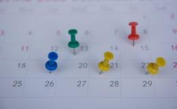 Les goupilles colorées de plan rapproché poussent l'inscription sur un calendrier Programme occupé Photographie stock