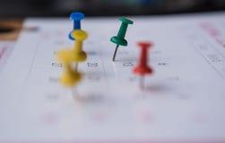 Les goupilles colorées de plan rapproché poussent l'inscription sur un calendrier Programme occupé Image stock