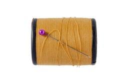 Les goupilles de couture roses avec la bobine brune filètent sur le fond blanc Photographie stock