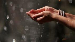 Les gouttes de l'eau chutent sur des mains du ` s de femmes Spectacle très enchanteur banque de vidéos