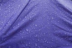 Les gouttes de pluie dans le bleu ont coloré le parapluie dans un jour obscurci Photographie stock libre de droits