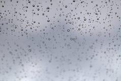 Les gouttes de pluie sur de verre lissent le congé dans la tache floue Images libres de droits