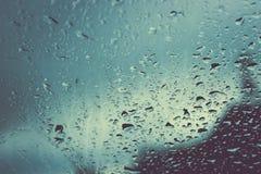 Les gouttes de pluie transparentes se trouvent sur le verre contre le ciel bleu Photographie stock libre de droits