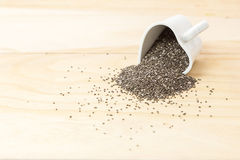 Les graines de Chia se renversent hors de la fin de tasse de forme de coeur sur le fond en bois photographie stock libre de droits