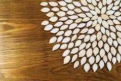 Les graines de citrouille contenues dans une fleur entoure sur le conseil foncé Pour a photographie stock libre de droits