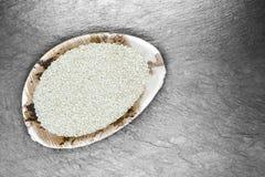 Les graines de sésame blanches dans le plat naturel de feuille de banane sur la surface en pierre blanche de fond avec l'espace l images stock