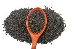 Les graines de sésame noires dans la cuillère en bois Images stock