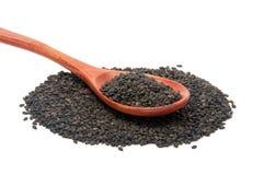 Les graines de sésame noires dans la cuillère en bois Photo stock