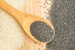 Les graines de sésame noires et blanches sur le fond en bois Photographie stock