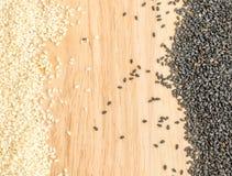 Les graines de sésame noires et blanches sur le fond en bois avec l'espace pour le texte Photographie stock libre de droits