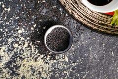 Les graines de sésame noires sont dispersées sur une table foncée photo libre de droits
