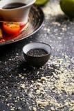 Les graines de sésame noires sont dispersées sur une table foncée photographie stock