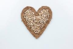 Les graines de tournesol se trouve au coeur fait de toile de jute Images stock