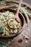 Les grains d'avoine et de blé entier s'écaillent dans la cuvette en bois Photos libres de droits
