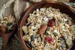 Les grains d'avoine et de blé entier s'écaillent dans la cuvette en bois Image libre de droits