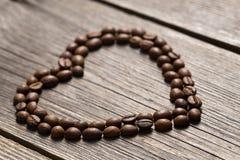 Les grains de café au coeur forment sur le fond en bois Image stock