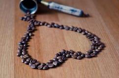 Les grains de café au coeur forment sur un fond en bois Photos stock