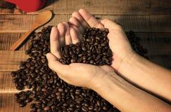 Les grains de café dans la main d'une femme montrent l'amour Photo stock
