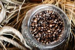 Les grains de café dans le vintage en verre cognent avec le fond de boîte en bois Image libre de droits