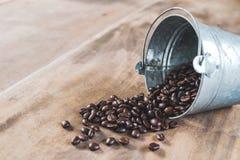 Les grains de café dans un métal bucket sur le plancher en bois Images libres de droits