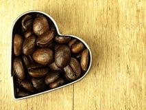 Les grains de café de coeur et se ferment sur la table de chêne en bois Photographie stock libre de droits