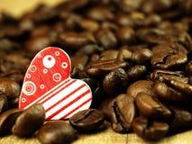 Les grains de café de coeur et se ferment sur la table de chêne en bois Photo libre de droits