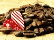 Les grains de café de coeur et se ferment sur la table de chêne en bois Photos stock