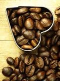 Les grains de café de coeur et se ferment sur la table de chêne en bois Photographie stock