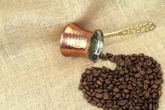 Les grains de café de forme de coeur ont débordé le pot de cuivre turc traditionnel de café sur une toile de jute Photos stock