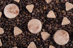 Les grains de café dispersés, avec le dessert léger de macaron, sucrent le coeur, jour de fond de tous les amants Photo stock