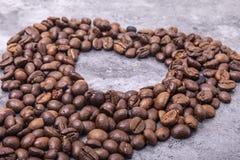 Les grains de café en forme de coeur sont sur la table Photos stock